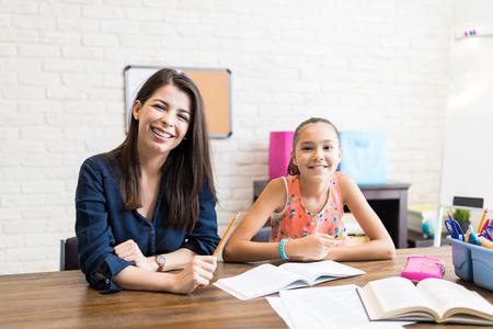 Portrait d'enseignant souriant donnant des leçons privées à la fille après l'école à table