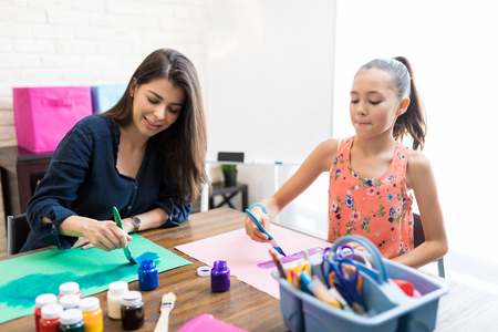 Mid adult teacher and student painting on drawing papers at table in home Stock Photo