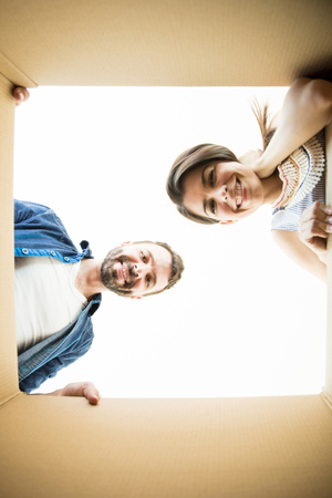 Directly below portrait of man and woman smiling while looking into moving box in new house