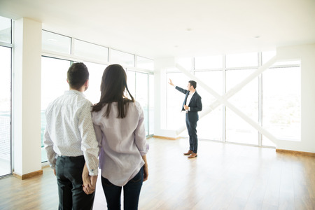 Couple holding hands while looking at estate agent showing window of new apartment