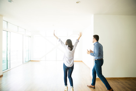 Excited mid adult man and woman entering into their new apartment