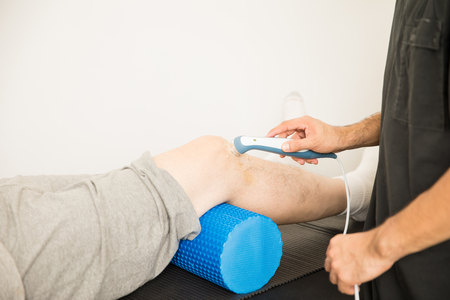 Cropped image of therapist using ultrasound probe to treat patients knee in hospital Stock Photo