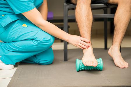 Section basse de la femme thérapeute aidant le patient à utiliser le rouleau de pied pour la fasciite plantaire et le soulagement de la douleur à l'hôpital