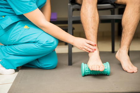 Low section of female therapist assisting patient to use foot roller for plantar fasciitis and pain relief in hospital Standard-Bild