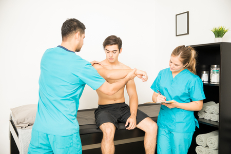 Young physiotherapist examining shirtless customers hand while coworker writing notes in clinic Stock Photo