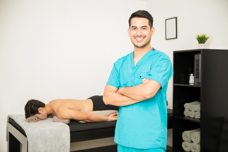 Smiling male physiotherapist standing arms crossed with patient lying in background at clinic Stock Photo