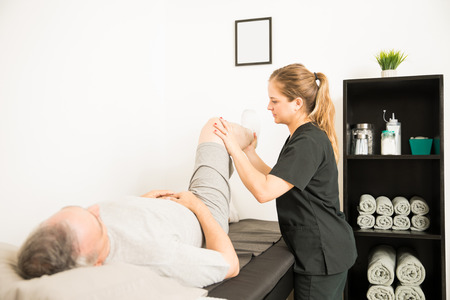 Female professional assisting elderly customer with lifting leg in hospital