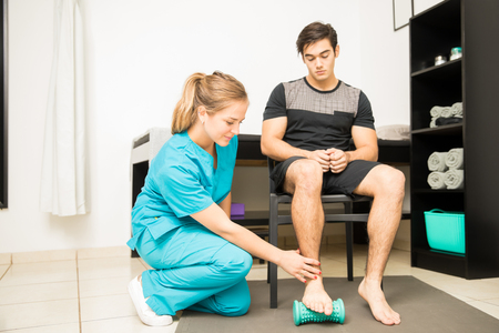 Full length of young physiotherapist treating plantar fasciitis in athlete at hospital