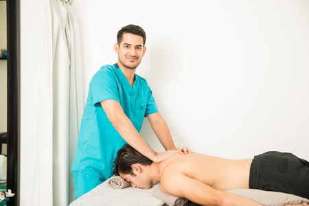 Confident physical therapist giving shoulder massage to patient lying in hospital Stock Photo