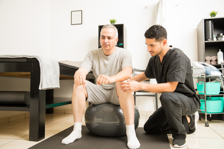 Male physiotherapist helping patient sitting on exercise ball in hospital
