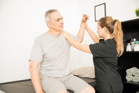 Female physiotherapist moving injured hand of elderly man in hospital