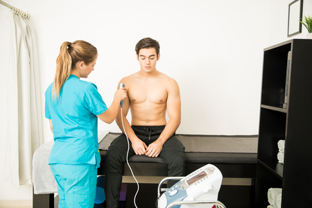 Shirtless athlete receiving electric ultrasound shoulder massage from physiotherapist in clinic