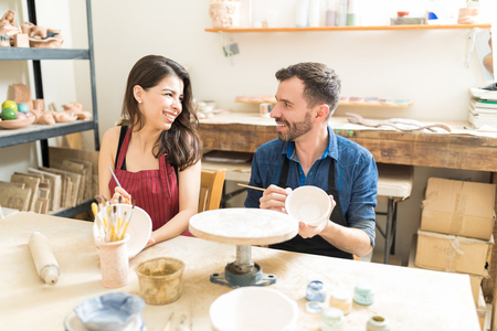Smiling mid adult couple having fun during pottery date in workshop Stok Fotoğraf