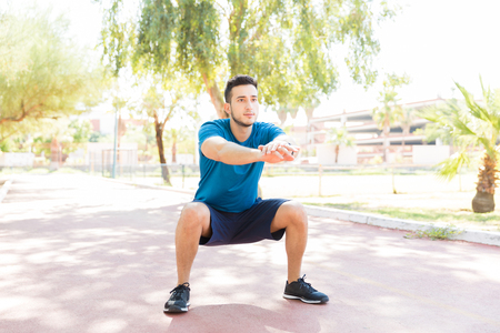 Determined young man performing squats before jogging on footpath in park