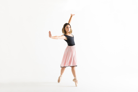 Full length of confident young ballerina dancing gracefully on white background Stock Photo
