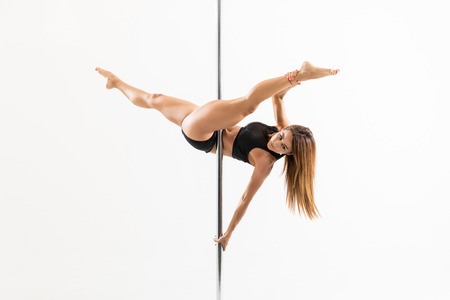 Sexy woman practicing some moves on a pole while dancing on white background