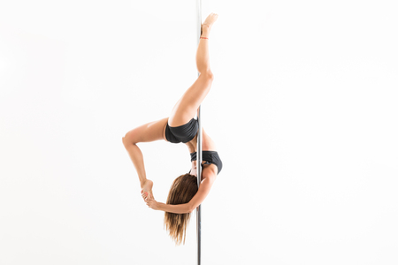 Mid adult woman practicing tricks while pole dancing against white background Stok Fotoğraf
