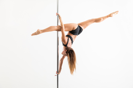 Strong female trainer stretching legs while pole dancing over white background