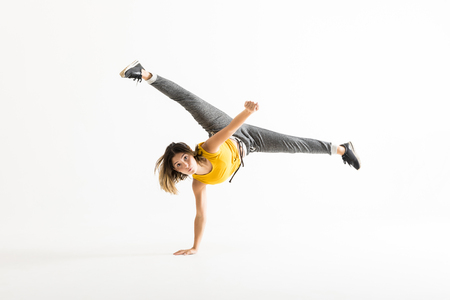 Attractive young woman doing a freeze breakdance move over white background Stock Photo