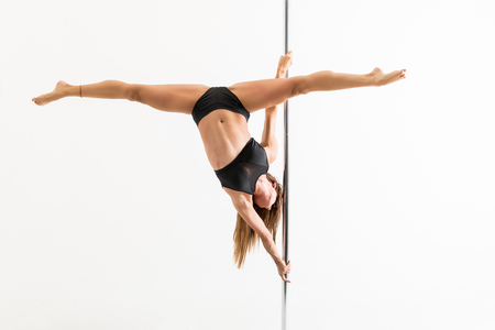 Enthusiastic female pole dancer with legs apart training over white background Stok Fotoğraf