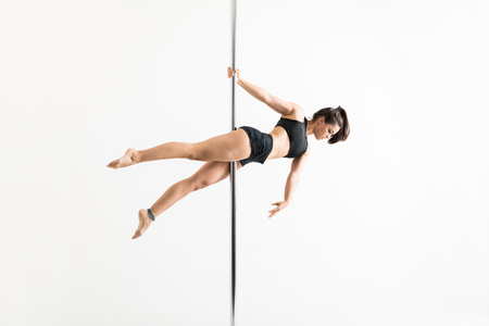 Full length of focused mid adult woman balancing herself on pole while dancing over white background