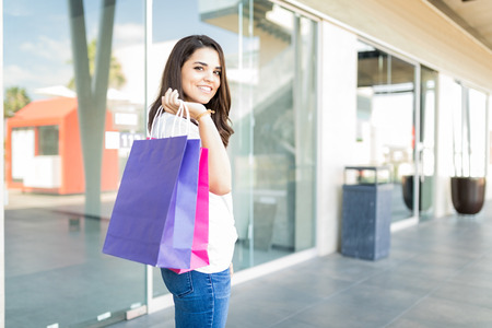 Satisfied mid adult woman carrying purple and pink paper bags in shopping mall