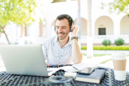 Smiling mid adult male using headphones connected to laptop while telecommuting in garden Stock Photo