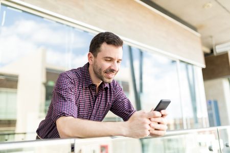 Mid adult man chatting online via high speed internet connected to smartphone in shopping mall