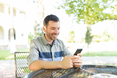 Mid adult male sending messages and photos in social networks using mobile phone at table in garden Фото со стока - 107949085