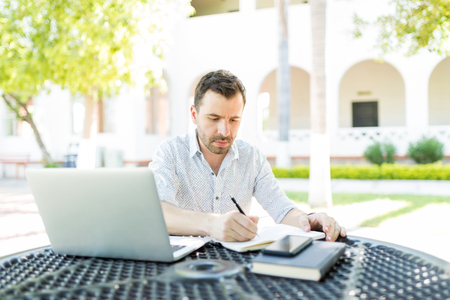 Self-employed man with laptop and books preparing schedule at table in garden