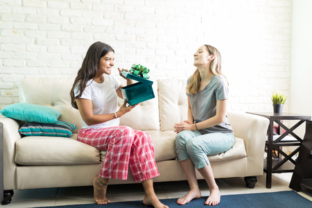 Happy young woman opening present while sitting with friend on sofa at home