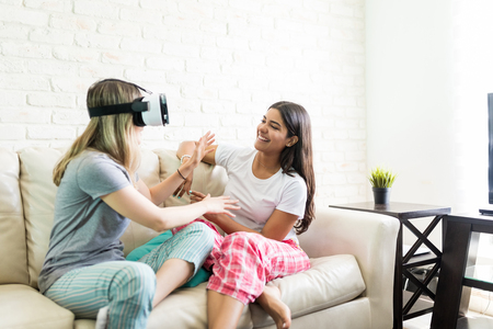 Happy young woman looking at friend wearing virtual reality headset at home Stock Photo