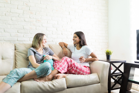 Happy young women revealing secrets of friends while enjoying pajama party at home Stock Photo