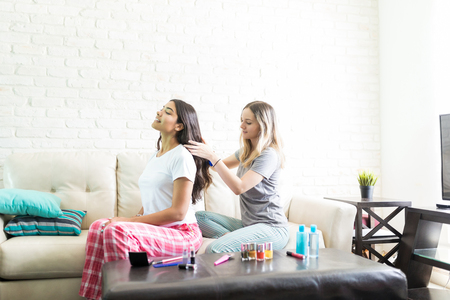 Female combing best friends hair while sitting on sofa at home Stock Photo
