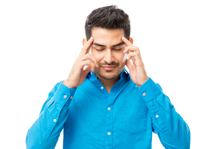 Handsome male massaging temples during headache against white background 스톡 콘텐츠