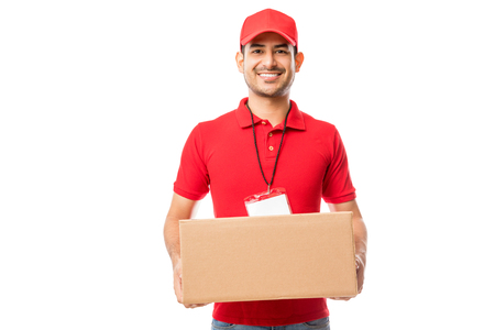 Portrait of smiling male carrying delivery package on white background