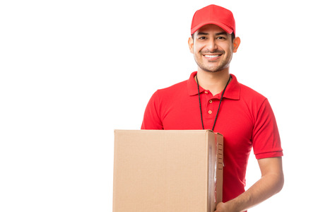 Young worker smiling while carrying parcel over white background