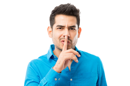 Handsome young man gesturing silence with finger on his lips over white background