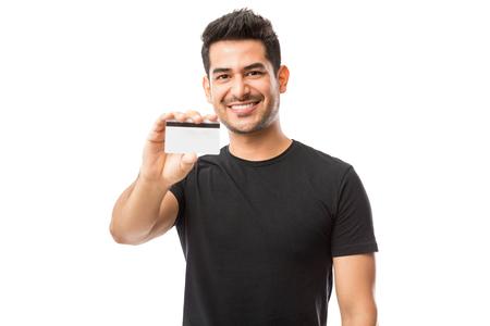 Chico atractivo que promueve la tarjeta de crédito mientras está de pie contra el fondo blanco.