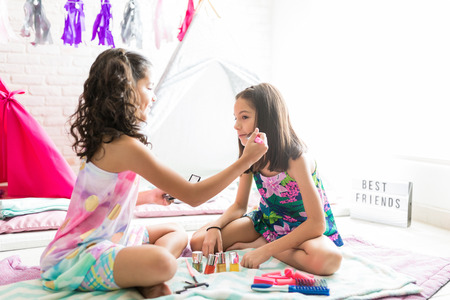 Cute preteen girl grooming friend for pajama party at home Reklamní fotografie