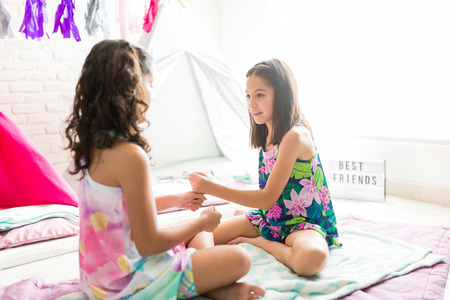 Best friends playing fist stacking game while sitting on duvets at sleepover party
