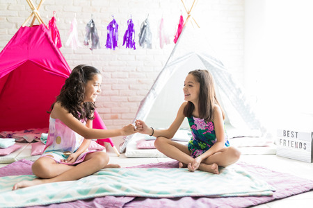 Happy friends taking pinky promises while sitting on duvets against tipi tents at home