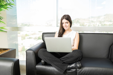 Portrait of confident human resource manager with laptop sitting in office lobby