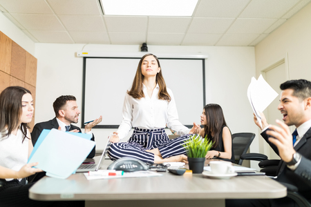 Young businesswoman meditating in lotus position while colleagues yelling during negotiation in office Stock Photo