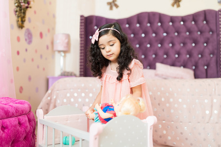 Female offspring putting doll to sleep in crib in her bedroom at home