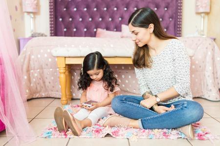 Babysitter keeping an eye on cute girl using smartphone in bedroom