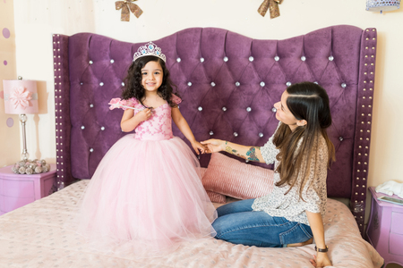Proud girl holding magic wand and wearing princess costume by mother on bed