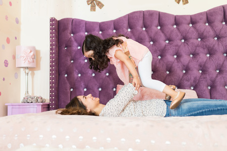 Side view of mom lifting preschool daughter in bedroom at home