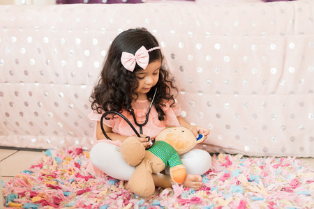 Female child doing treatment of teddy bear with stethoscope in bedroom