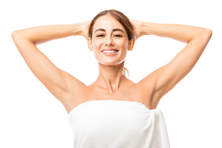 Headshot of good looking woman showing clean armpits after laser treatment against white background